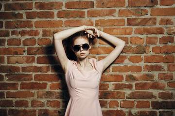 woman with glasses, brick wall