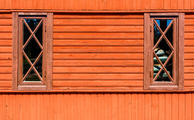 Red wooden wall with windows and mullions.