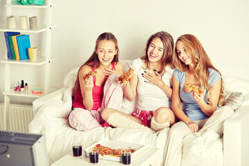 happy friends eating pizza and watching tv at home