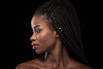 Dark skinned model with turning head to the left side on black backstage. Close up portrait of woman with naked shoulders. Portrait of dark skinned female with bright make up and stylish hair.