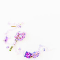 Bouquet of pink flowers, paper box and shabby tapes on white background. Flat lay, top view. Holidays background