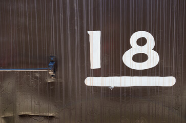 Painted number 18 on corroded black train car