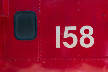 Red metal texture with window and 158 number from train side