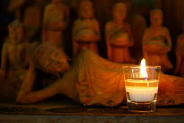 Aroma candle placed in front of handcraft wooden statue of reclining buddha