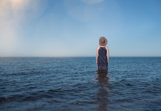 rear view of young blonde caucasian woman wearing a blue dress and a summer hat standing in shallow ocean water under clear blue