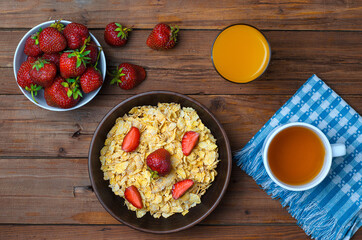 The concept of a healthy diet: cornflakes, strawberries, a glass of juice and a cup of tea on an old wooden table.