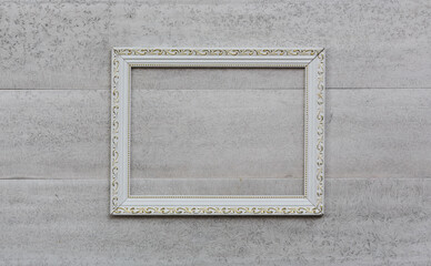 White, old, victorian, baroque frame on an old, weathered, white wall