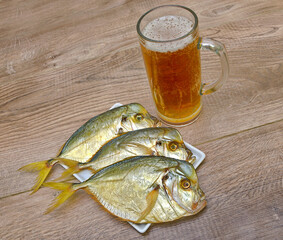 Dried fish and a glass of beer on a wooden table.