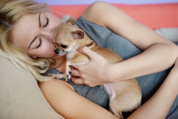 Teenage girl with her dog laying in bed