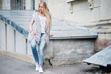 Stylish blonde woman wear at jeans and girl sleeveless with white shirt against street. Fashion urban model portrait.