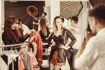 Stylist putting clothes on model