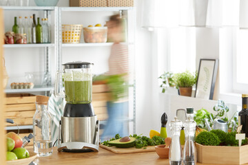 Kitchen table with vegetables and blender