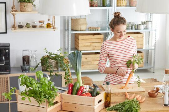 Woman peeling a carrot in kitchen