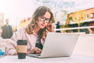 Front view.Young woman in glasses is sitting at table in street cafe and using laptop. Businesswoman working.
