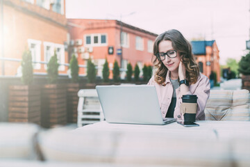 Young businesswoman in glasses is sitting at table in street cafe and working on laptop.