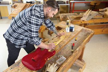 Craftsman sanding a guitar neck in wood at workshop