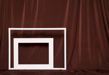 Two empty picture frames on background of brown cloth.