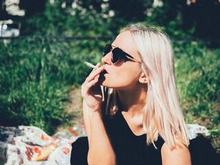 Close-Up Of Beautiful Woman Smoking On Field