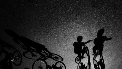 Shadow Of Boys Riding Bicycles On Street During Sunny Day