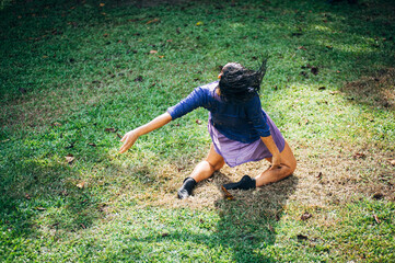 Rear View Of Woman Dancing On Grass