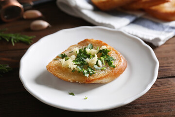 Tasty bread slice with garlic and herbs on plate