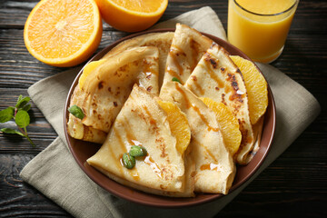 Tasty pancakes with orange slices on plate