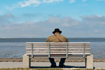 Mann mit Hut, sitzt auf einer Bank am Meer