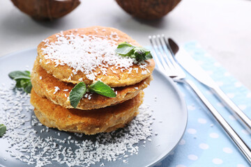 Plate with tasty homemade coconut pancakes and mint on table