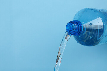 Water pouring from plastic bottle on color background