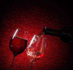 Wine pouring into a glass on red background