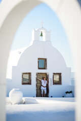Young attractive woman posing by the church door, Oia, Santorini, Greece