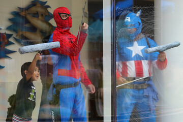 Dominic helps window-washers dressed as superheroes as they work at Rady Children's Hospital in San Diego