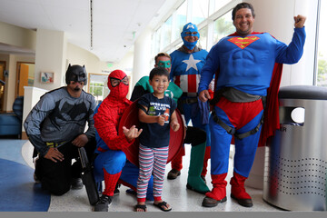 Dominic poses for a picture with window-washers dressed as superheroes as they work at Rady Children's Hospital in San Diego