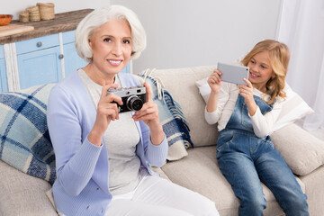Grandmother taking pictures with film camera and girl with mobile or smart phone. Happy ladies smiling for camera.