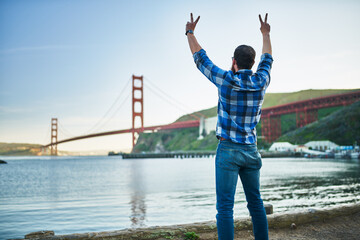 cool guy cheering and making peace sign in front of golden gate bridge in san francisco