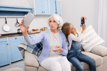 Grandmother and granddaughter use each other's gadgets for taking pictures while sitting on sofa or couch at home.