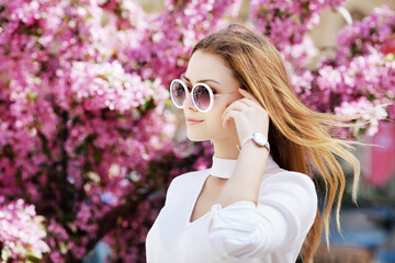 Outdoor close up portrait of young beautiful fashionable girl posing in street, near blooming tree with pink flowers. Model looking aside, wearing stylish round glasses, wrist watch. Copy, empty space