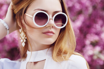 Outdoor close up portrait of young beautiful fashionable girl posing in street, near blooming tree with pink flowers. Model looking aside, wearing stylish glasses, wrist watch. Copy, empty space