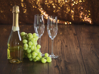 Two flutes bottle of champagne and cluster of grapes on a wooden , sparkling bokeh in the background.
