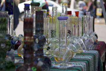 Close Up View Glass Bongs on Flea Market Table, Sunlit Out of Focus Background, Backdrop,  Copy Space Use Overlay for Text - Eugene, Oregon, USA