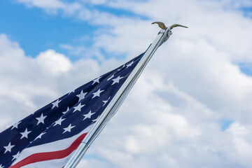 looking up at American flag waving proudly in bright blue sky