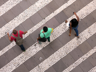 People walking over pattern sidewalk - birds eye