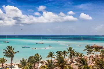 Fototapete - Sail and motor boats criss cross the bay at Palm Beach, Aruba