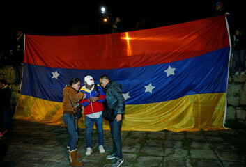 Venezuela's residents in La Paz stand in front a Venezuelan national flag turned upside as protest against President Nicolas Maduro government during a vigil in La Paz