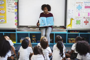 Kindergarten students sitting on the floor listening to story telling