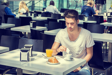 Attractive Young Man Eating Breakfast, Drinking Coffee and Having Orange Juice and Pastry
