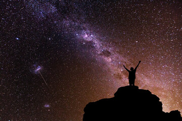 Milky Way. Beautiful night sky with stars and silhouette of a standing alone man on the mountain.