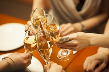 Women are toasting with champagne glasses