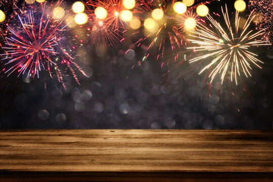 Empty wooden table in front of fireworks background