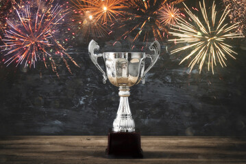 low key image of trophy over wooden table and dark background, with abstract fireworks.